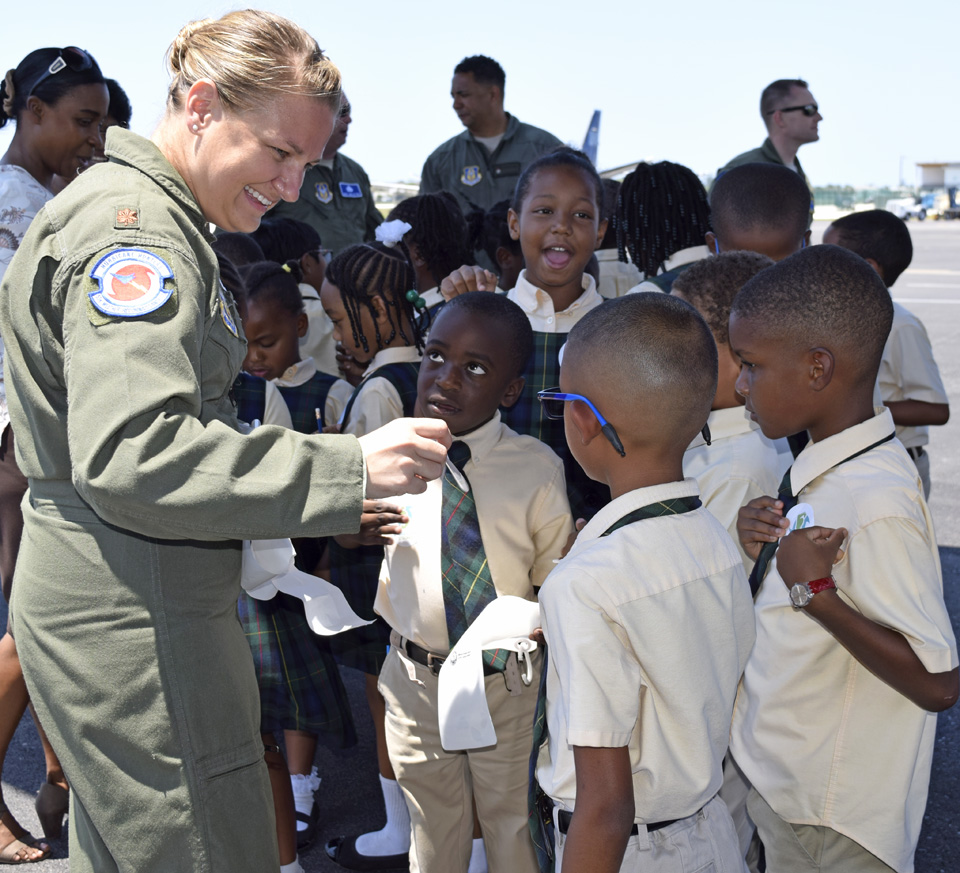 Crew members give Hurricane Hunter Stickers to the children.