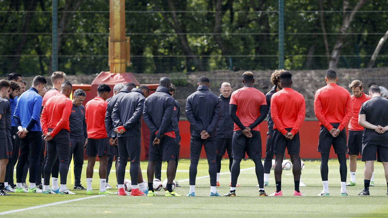 Manchester United's Wayne Rooney, center facing, stands alongside his teammates ahead of a training session at the AON Training Complex in Carrington, England, Tuesday, for a minute of silence to remember the victims after an apparent suicide bomber attacked an Ariana Grande concert on Monday night. (Martin Rickett/PA via AP)