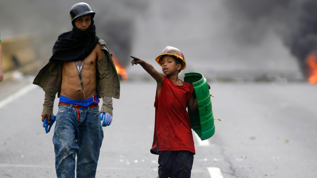 A demonstrator and boy wearing a helmet and holding a shield, walk on a blocked highway as a barricade burns in the background, during a national sit-in against President Nicolas Maduro, in Caracas, Venezuela, Monday, May 15, 2017. (AP Photo/Fernando Llano)