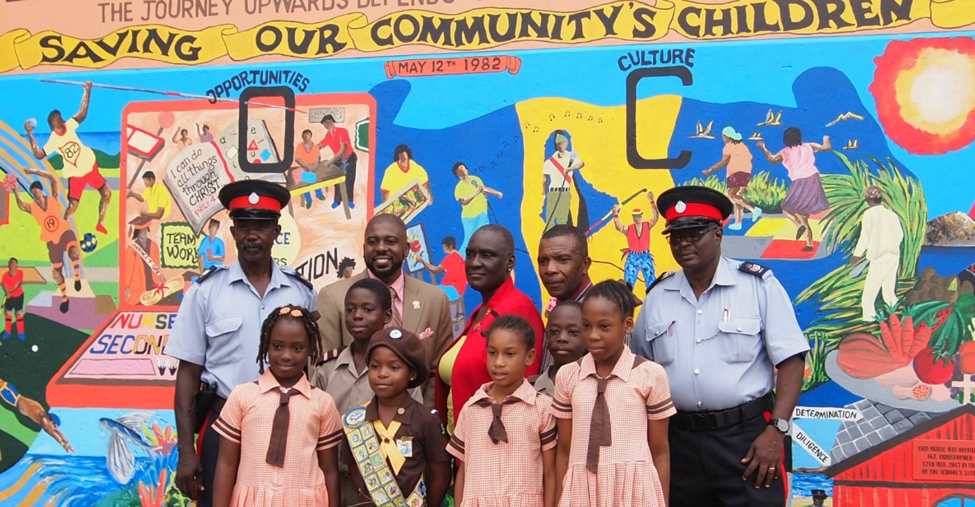 Back row, L-R: Sargeant Christopher Griffith, Dr. Reverend Adrian Smith, Principal, Beverley Parris, Mural designer, Patrick Craigwell  Front row: Students who assisted with the painting of the mural
