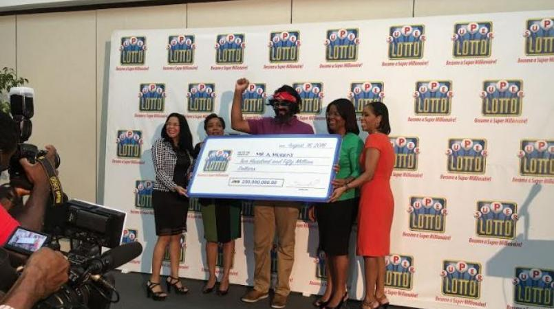 A previous winner of the Super Lotto jackpot poses with his symbolic cheque.