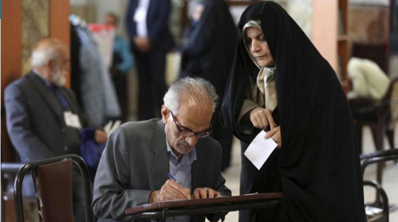 A man fills out his ballots to vote in the presidential and municipal council election in Tehran, Iran, Friday, May 19, 2017. Iranians began voting Friday in the country's first presidential election since its nuclear deal with world powers, as incumbent Hassan Rouhani faced a staunch challenge from a hard-line opponent over his outreach to the wider world.