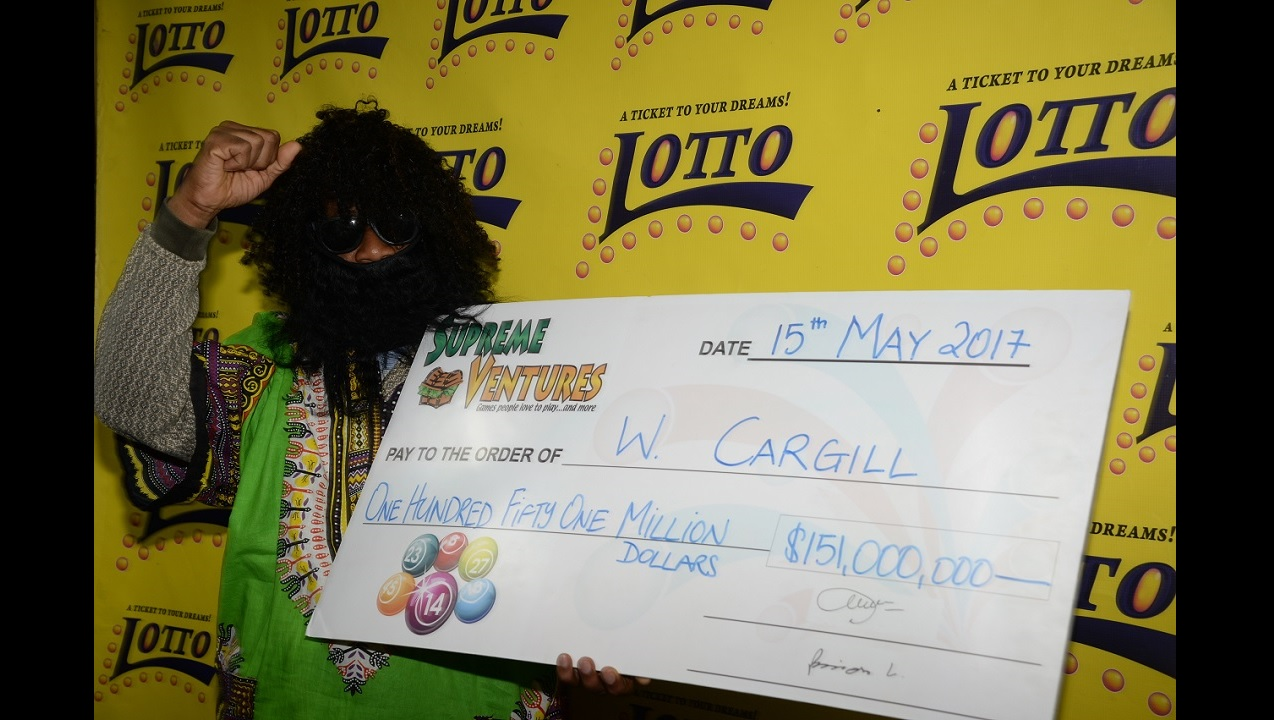 Lotto winner, W Cargill poses with a symbolic cheque representing the $151 million jackpot he won on May 6. Cargill, an avid player of Lotto for the past 20 years, purchased his winning ticket at the Supreme Ventures-owned Acropolis Gaming Lounge located on East Kings House Road. (PHOTO: SVL)