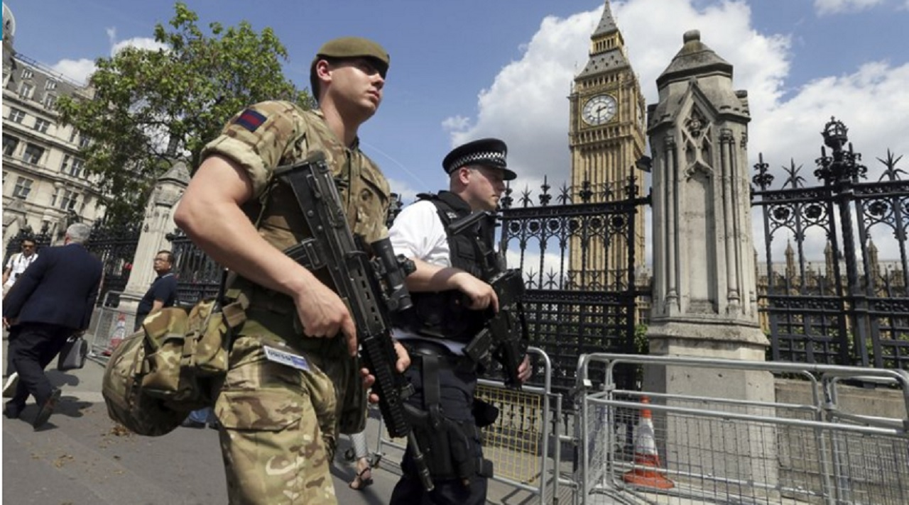 A member of the army joins police officers in Westminster, London, Wednesday, May 24, 2017. Britons will find armed troops at vital locations Wednesday after the official threat level was raised to its highest point following a suicide bombing that killed more than 20, as new details emerged about the bomber.
