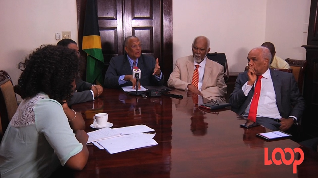 Opposition Leader Dr Peter Phillips (centre) addresses journalists on the controversial land deal.