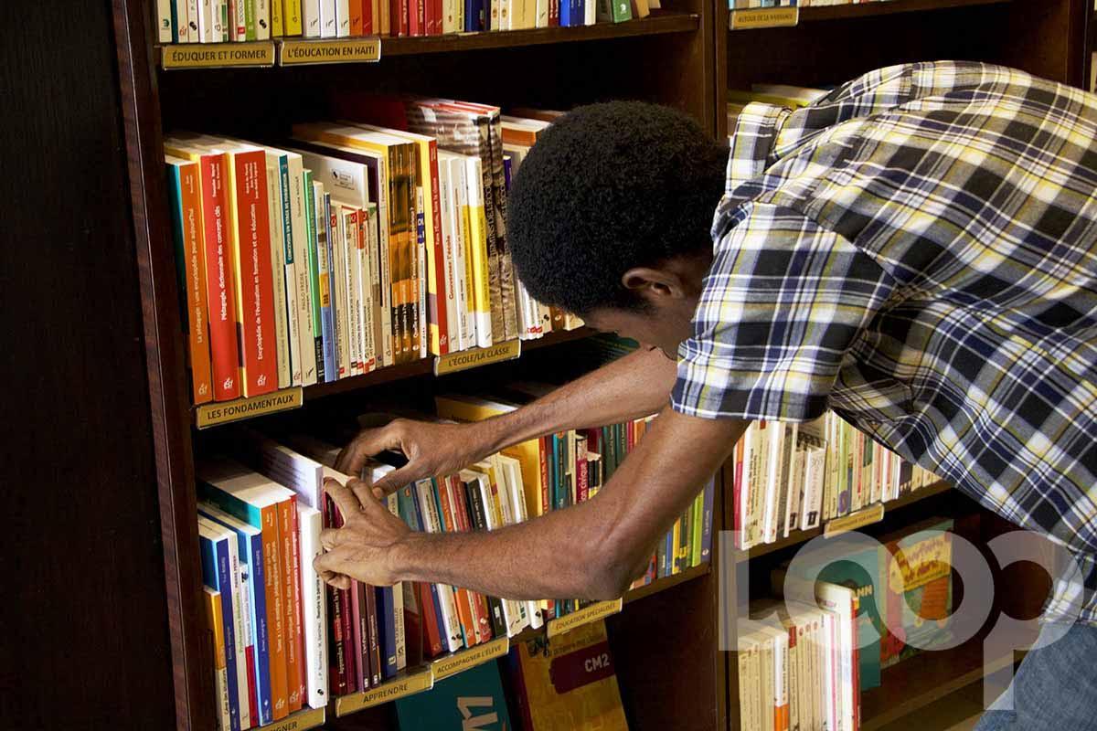 Un jeune consulte de rayons de livres dans une librairie/ Crédit photo: Vladjimir Legagneur