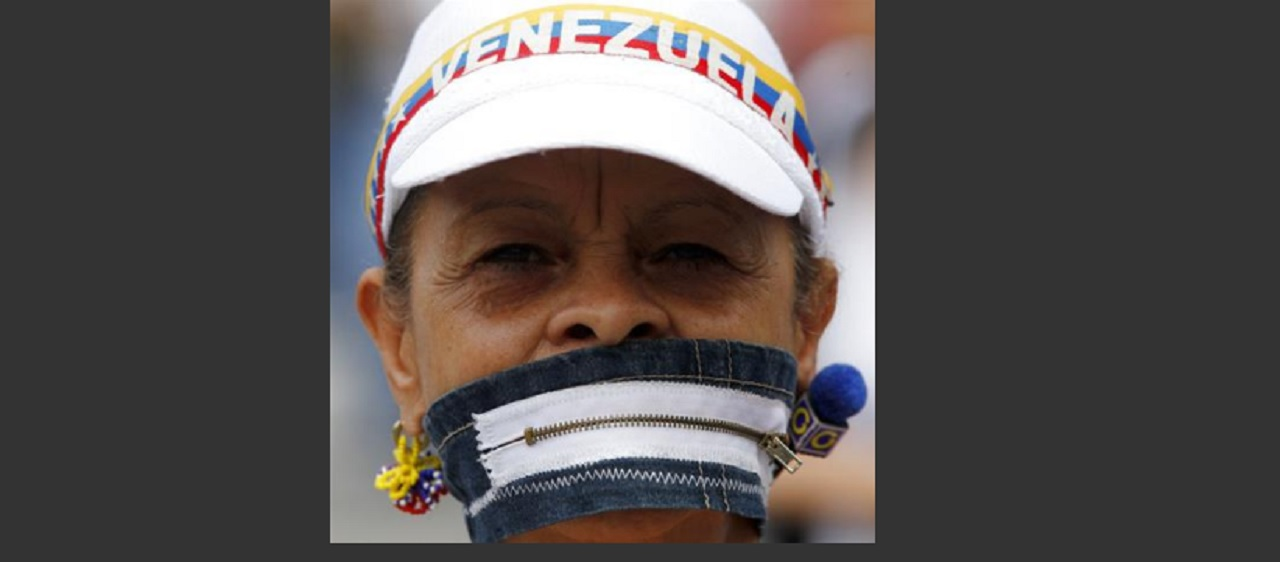 An anti-government protesters covers her mouth with a zipper during a women march against repression in Caracas, Venezuela, Saturday, May 6, 2017. Weeks of violent protests calling on President Nicolas Maduro to step down have left dozens of people dead.