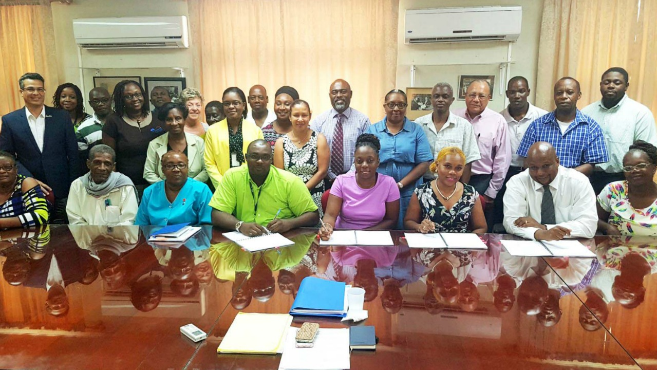 BHTA's Roseanne Myers and BWU's Toni Moore and Dwaine Paul (seated – third fourth and fifth from right) sign the three-year collective agreement while other members of the BHTA including First Vice Chairman Gerry Lewis and CEO Rudy Grant,as well as other BHTA and BWU representatives and industry workers look on.