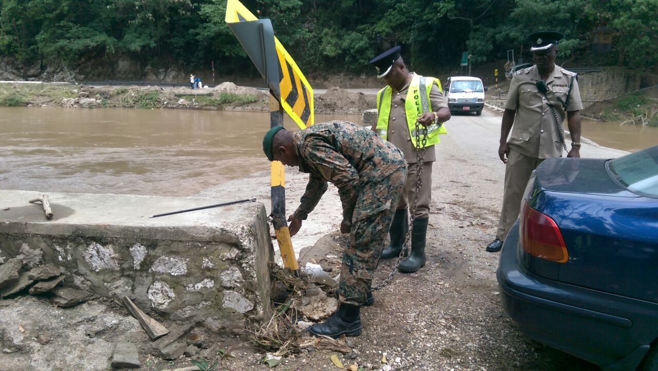 Members of the security forces assess the damage left by flood rains during a tour of the Bog Walk Gorge earlier this week.