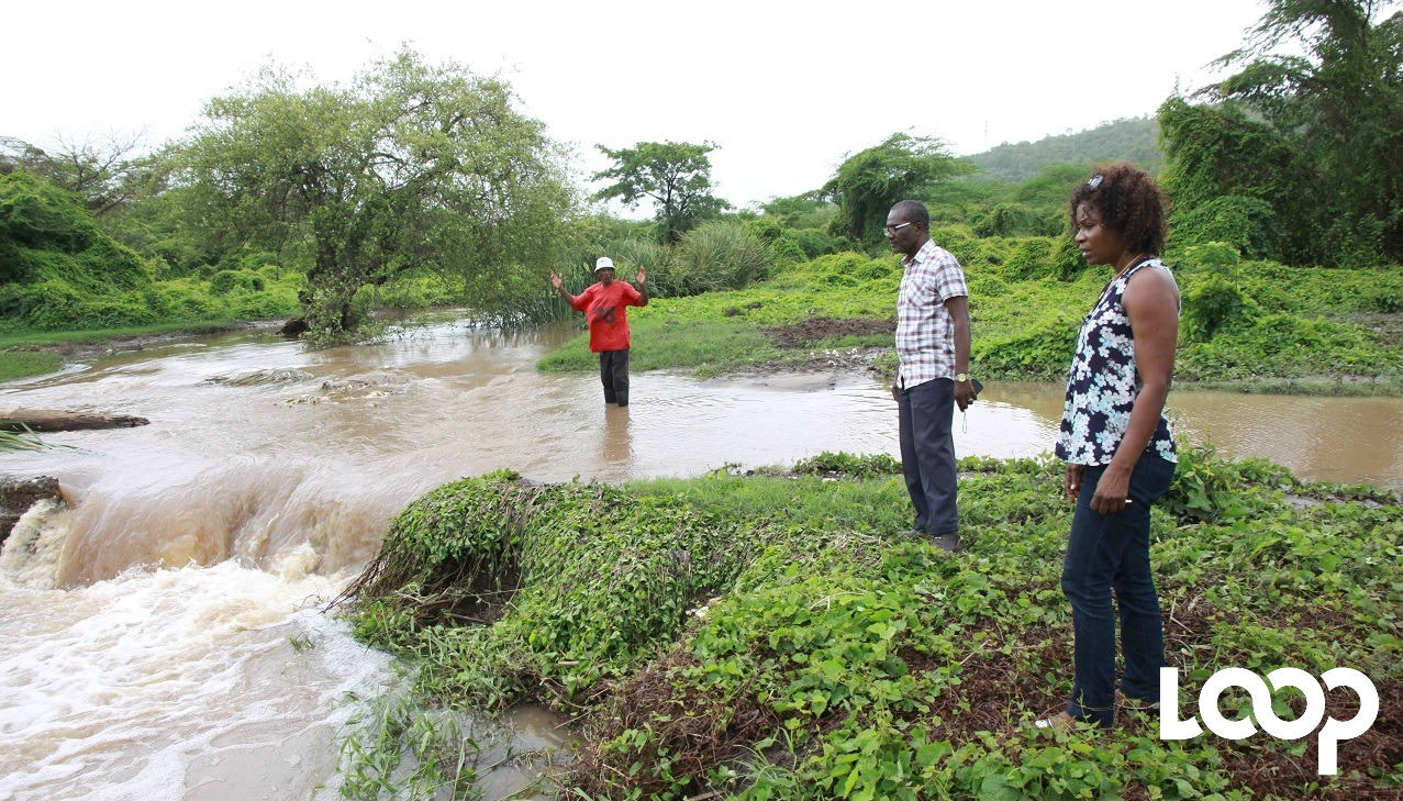 A resident shows JLP Councillor of the Race Course division Pauline Reynolds, and Lloyd Samuels (centre) of the Clarendon parish council, the water at the Fisher Road fording after heavy rains on Monday (FILE).