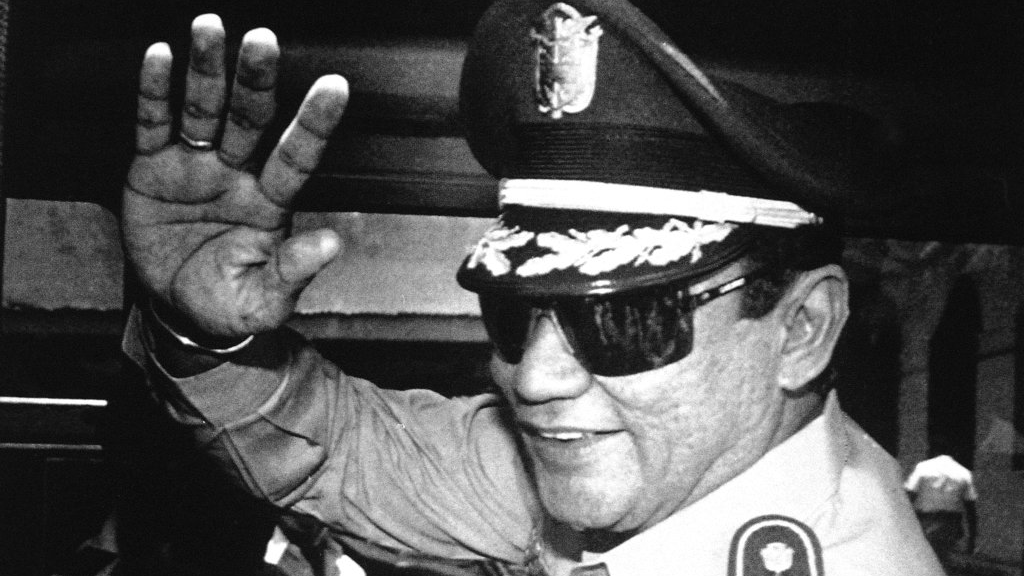 In this Aug. 31, 1989 file photo, Gen. Manuel Antonio Noriega waves to newsmen after a state council meeting, at the presidential palace in Panama City, where they announced the new president of the republic. (AP Photo/Matias Recart, File)