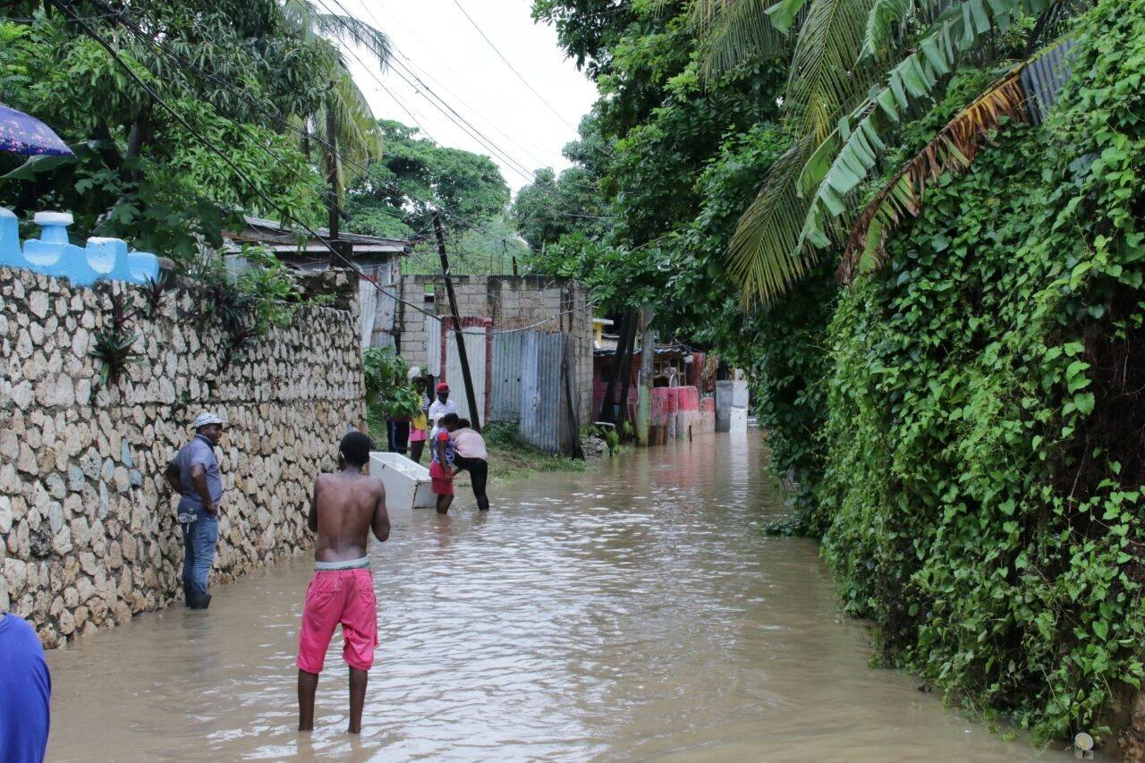 Spanish Town residents stand in ankle-deep water following heavy rains earlier this week.