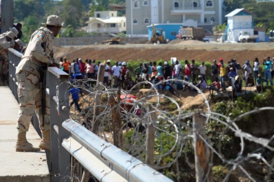 Des soldats dominicains surveillent les haïtiens déplacés le long de la frontière haitiano-dominicaine.   Credit photo: http://www.brownpoliticalreview.org