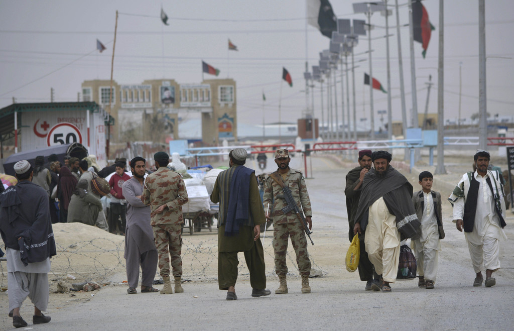 In this March 20, 2017 file photo, Pakistani paramilitary soldiers stand guard while people wait for the opening of the border crossing in Chaman, Pakistan. (AP Photo/Matiullah Achakzai, File)