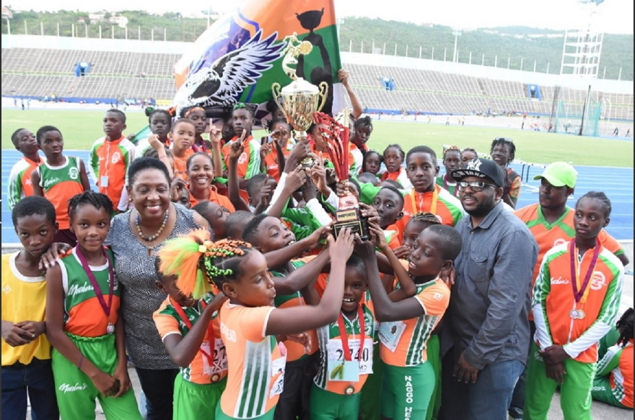 Sports Minister Olivia Grange (3rd left) poses with members of the Naggo's Head track and field team after they were presented with the winning trophy after securing their third straight INSPORTS Primary School Athletics Championships at the National Stadium on Saturday.