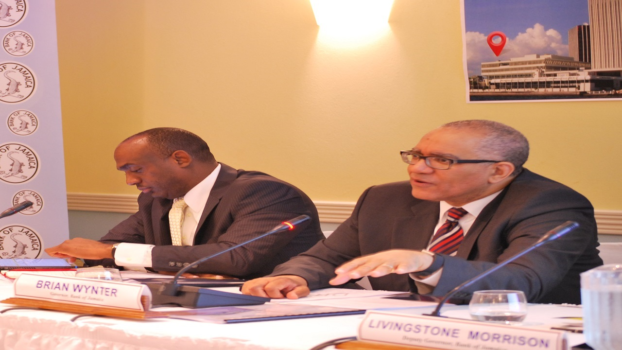 BOJ Governor Brian Wynter (right) addresses journalists at the quarterly press briefing.