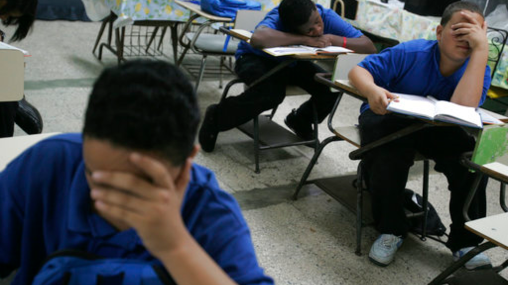 In this Jan. 24, 2008 file photo, students sit at their desks inside a classroom, at Republica del Peru middle school, in San Juan, Puerto Rico. The U.S. territory is closing 184 public schools, officials announced Friday, May 5, 2017, in a move expected to save millions of dollars amid a deep economic crisis. (AP Photo/Brennan Linsley, File)