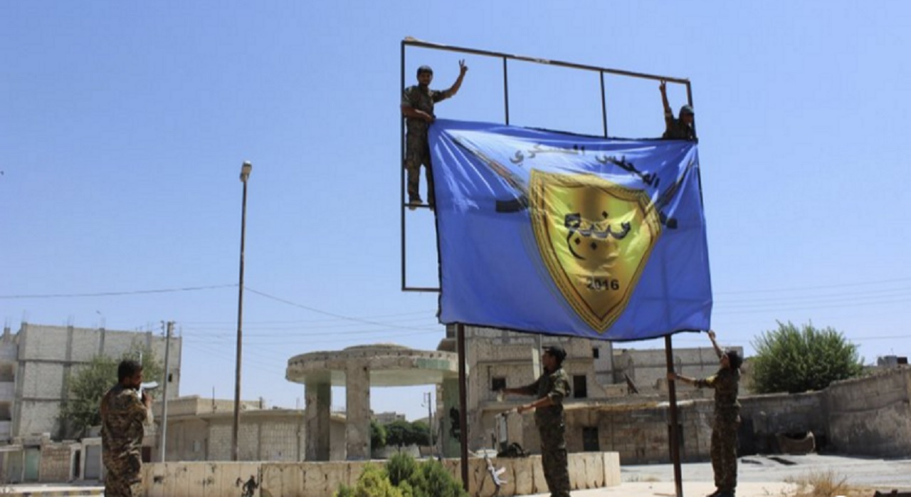 In this file photo released on Aug. 8, 2016 by Hawar news, the news agency for the semi-autonomous Kurdish areas in Syria (ANHA), shows Kurdish-led Syria Democratic Forces raising their flag after driving Islamic State militants out of the area, in Manbij, Syria.