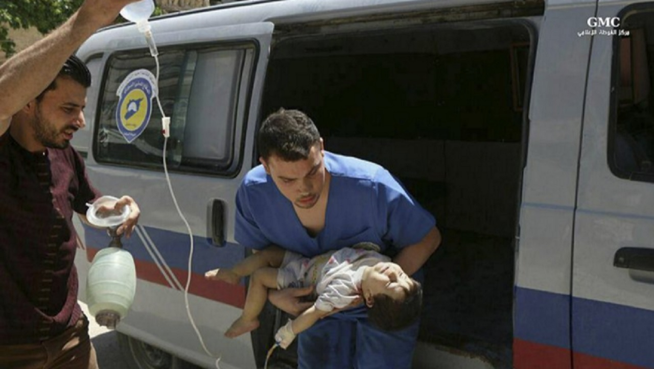 This photo provided by the Syrian anti-government activist group Ghouta Media Center, which has been authenticated based on its contents and other AP reporting, shows a Syrian nurse carrying an injured child who was wounded by Syrian government forces shelling, in the Hamouriyya neighborhood, an eastern suburb of Damascus, Syria, Tuesday, May 16, 2017.