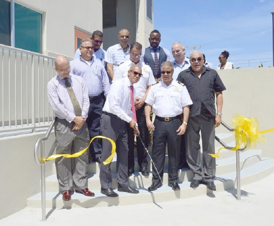 Finance Minister Marco Archer snips yellow ribbon at official opening of new Customs facility