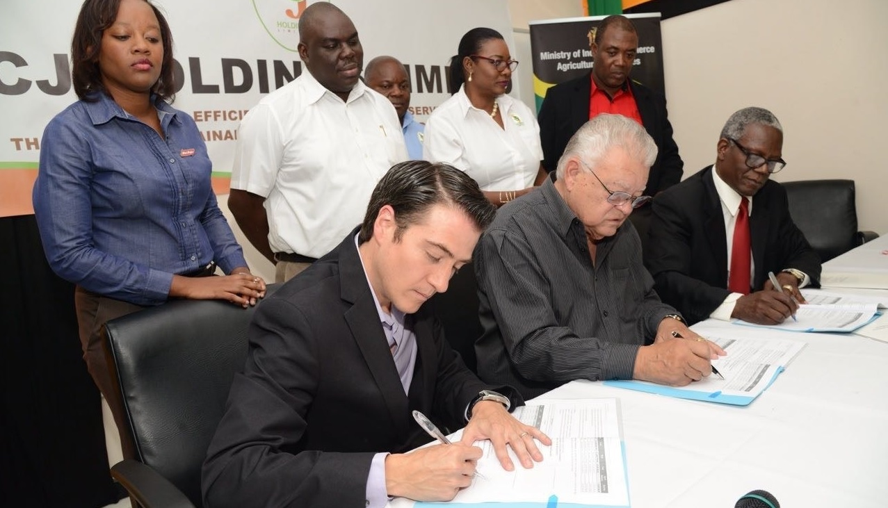 (From left seated) Ricardo Nuncio, managing director of Red Stripe; Industry Minister Karl Samuda and Wentworth Charles, chairman of the Sugar Company of Jamaica, sign documents for the leasing agreement.