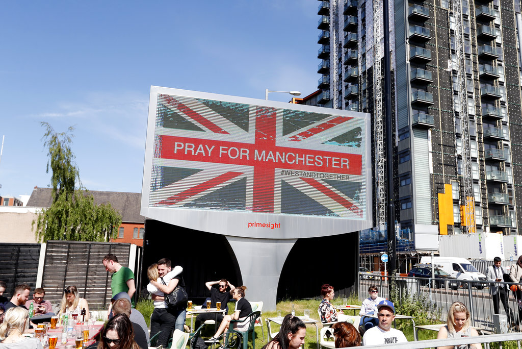 People sit under a billboard in Manchester city centre, Tuesday May 23, 2017, the day after the suicide attack at an Ariana Grande concert that left 22 people dead as it ended on Monday night. (AP Photo/Kirsty Wigglesworth)