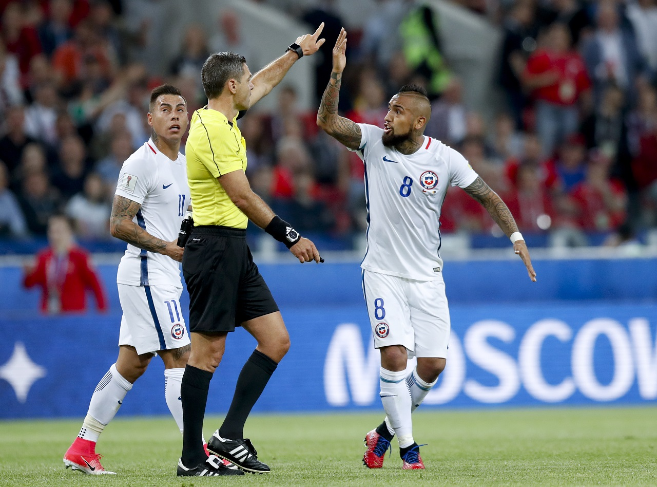 Chile's Arturo Vidal, right, and Eduardo Vargas argue with referee Demir Skomina during the Confederations Cup, Group B soccer match between Cameroon and Chile, at the Spartak Stadium in Moscow, Sunday, June 18, 2017.