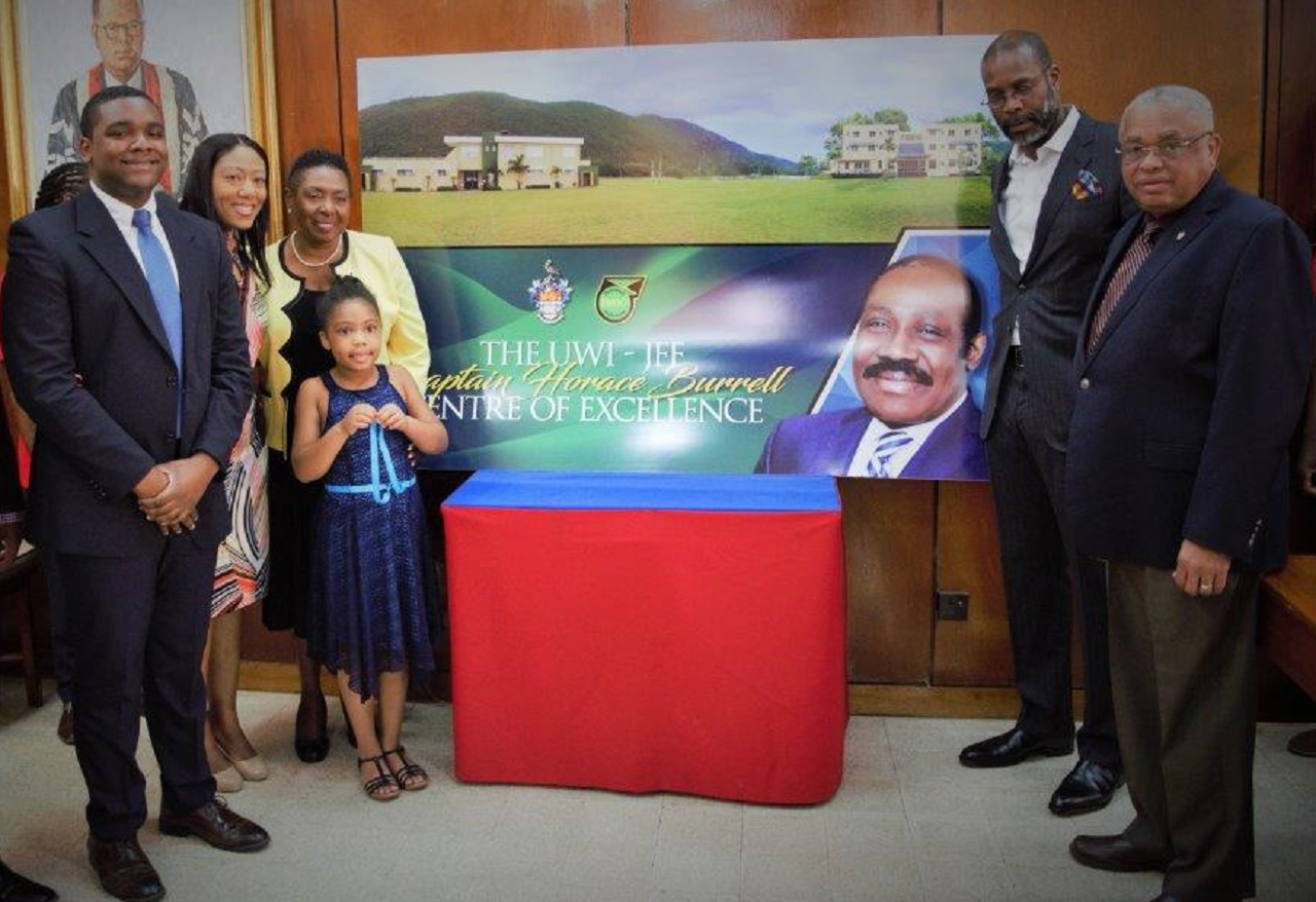 UWI Principal Professor Archibald McDonald (first right) and JFF Vice-President Garfield Sinclair (2nd right)  stand beside the JFF/UWI Captain Horace Burrell Centre of Excellence display sign, honouring the late JFF president. Also included in the photo are (from left) Captain Burrell's son Romario Burrell, daughter Dr Tiphani Burrell-Piggott, Minister of Sports Olivia Grange and Zuri Piggott, granddaughter of Captain Burrell.