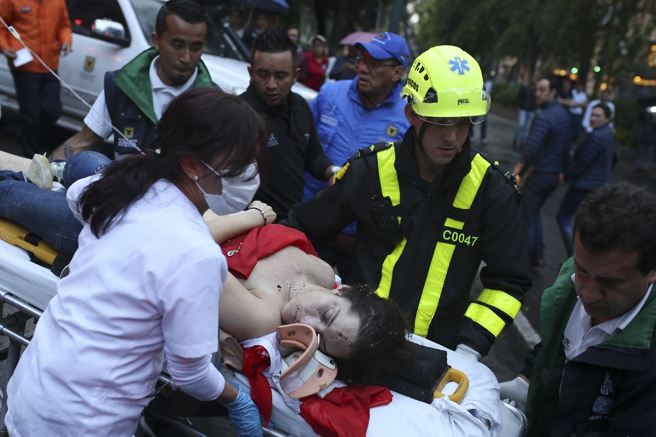An injured woman is evacuated on a gurney after an explosion at the Centro Andino shopping center in Bogota, Colombia, Saturday, June 17, 2017. Authorities reported at least 3 persons killed with scores more injured.