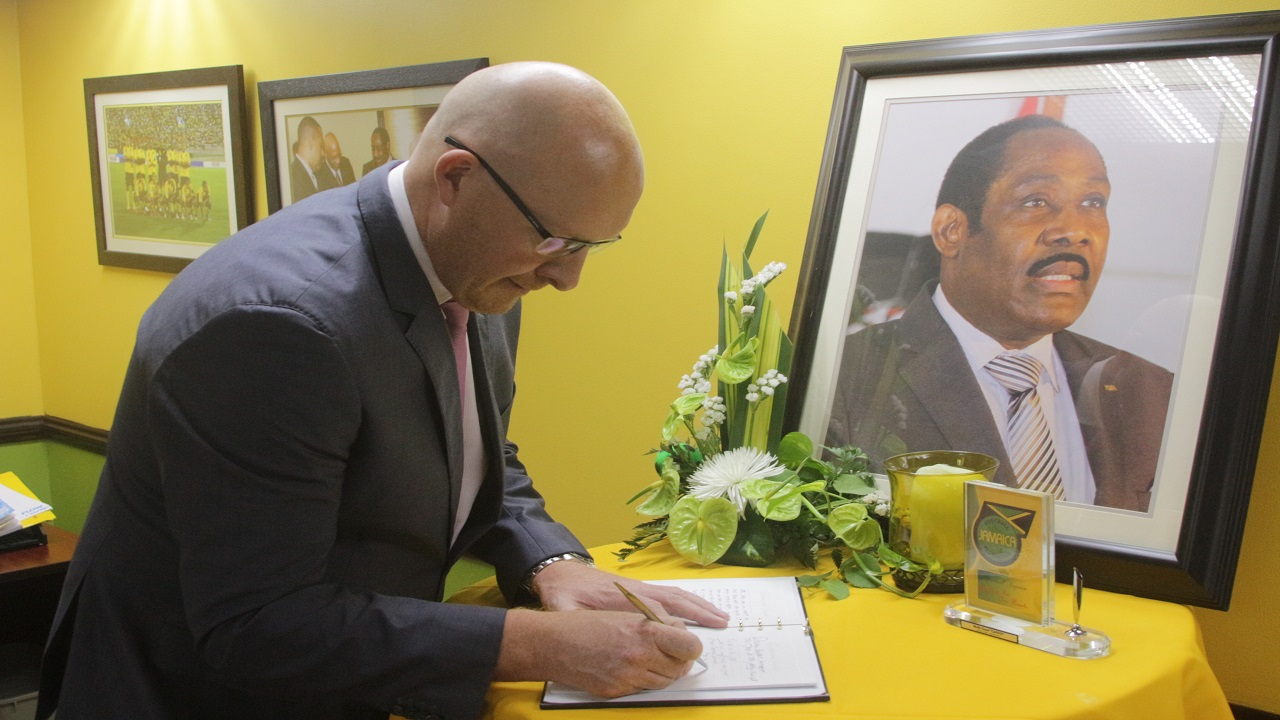 David Butler, chief executive officer of Digicel Jamaica, signs the condolence book for the late Jamaica Football Federation president Captain Horace Burrell at the JFF headquarters in Kingston on Friday. (PHOTO: Marlon Reid)
