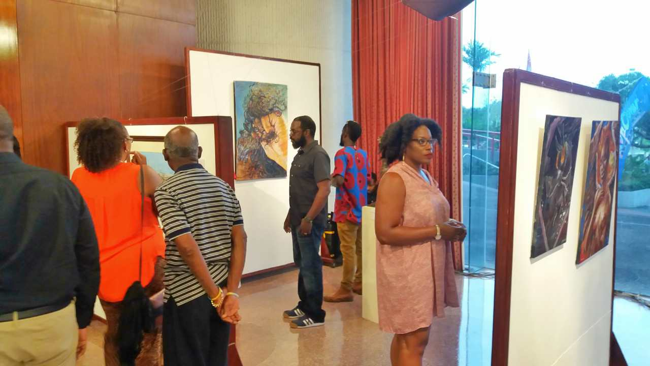 Persons browse the pieces on display at the Crop Over Visual Arts Festival 2017.