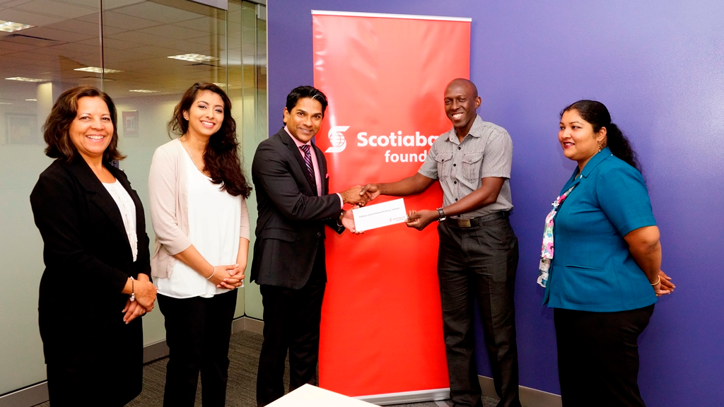 Peter Ghany - Director, Scotiabank Foundation, presents the financial contribution for new steelpan equipment to Febeau Government Primary School's Neil Simon - Music Teacher. Also in the photo are L-R: Cheryl Hernandez – Scotiabank Foundation Support Officer, Kameel Baksh-Edwards – General Manager, Scotiabank Foundation and Ayesha Mustafa – Teacher, Febeau Government Primary School.