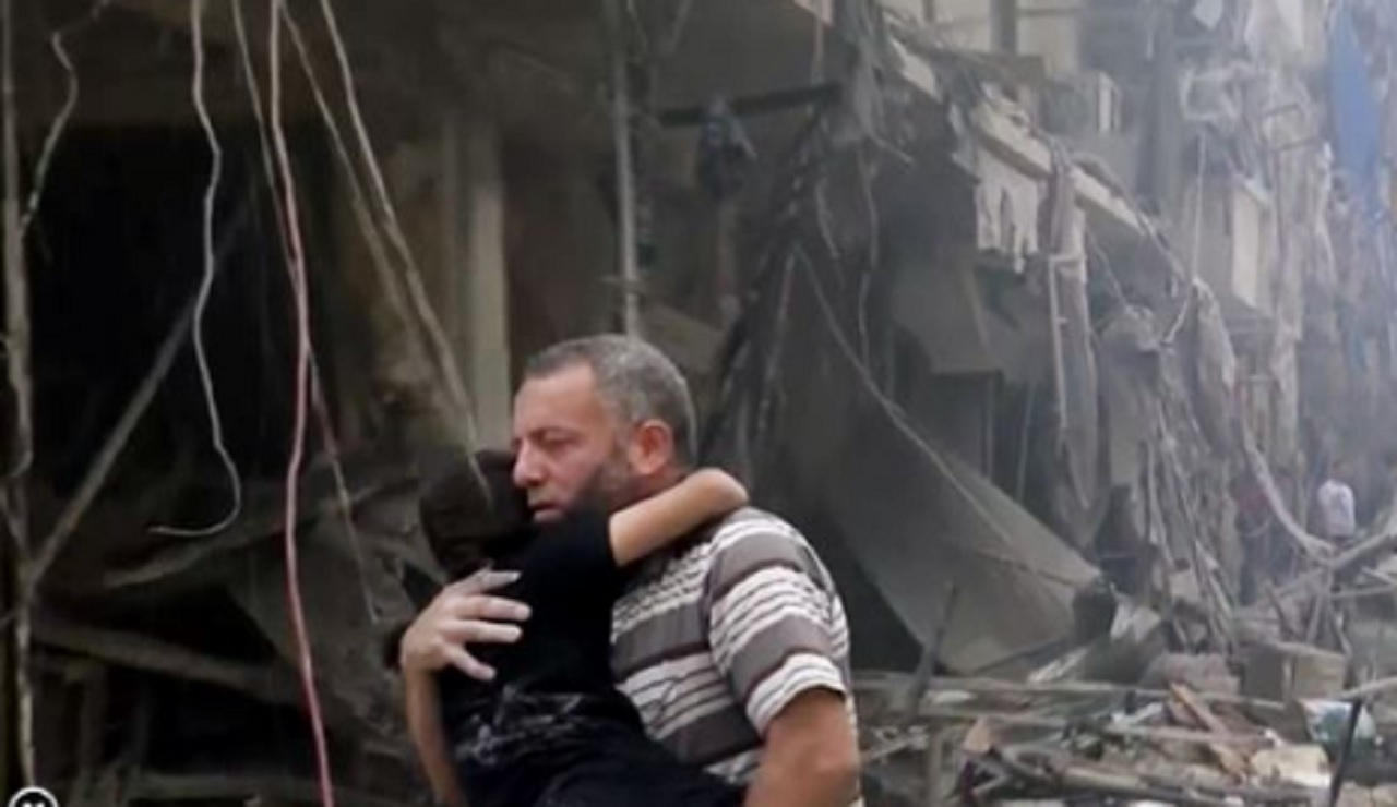 In this image made from video and posted online, a man carries a child after airstrikes hit Aleppo, Syria, Thursday, April 28, 2016.