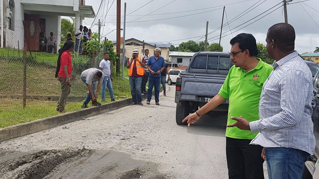 Minister of Rural Development and Local Government Kazim Hosein and Moruga/Tableland MP Lovell Francis discuss road repairs in the area.