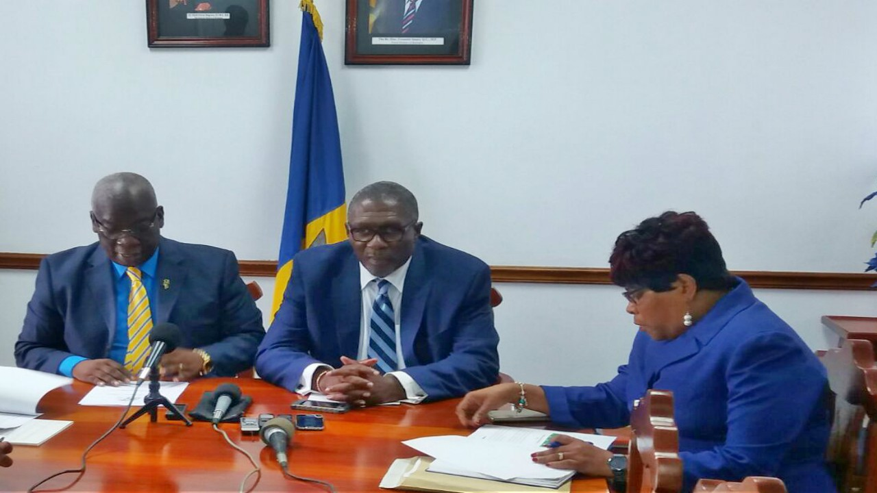Minister of Education (left) Ronald Jones, speaking to members of the Media, while Parliamentary Secretary in the Ministry of Education, Harry Husbands (centre) and Chief Education Officer, Karen Best (right) listen.