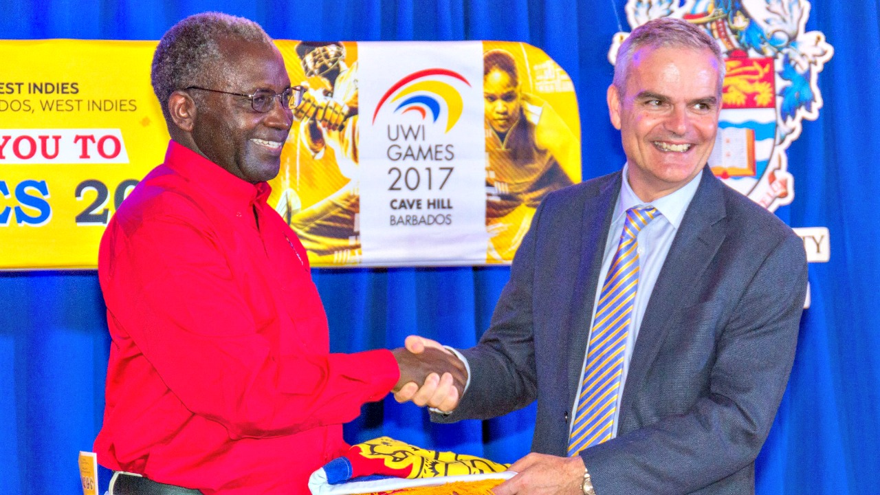 Professor Ishenkumba Kahwa, UWI Mona Deputy Campus Principal, receives The UWI Inter-Campus Games flag in commemoration of the campus' win from Deputy Principal of the Cave Hill Campus, Professor Clive Landis.