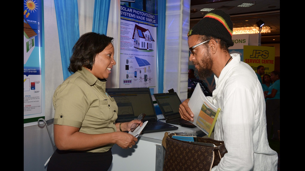 Denise Tulloch (left), Senior Research Officer at the Petroleum Corporation of Jamaica (PCJ) interacts with a consumer who visited the PCJ's booth during the 2016 PCJ Jamaica Alternative Energy Expo to get a demonstration of the PCJ's Solar Energy Calculator.