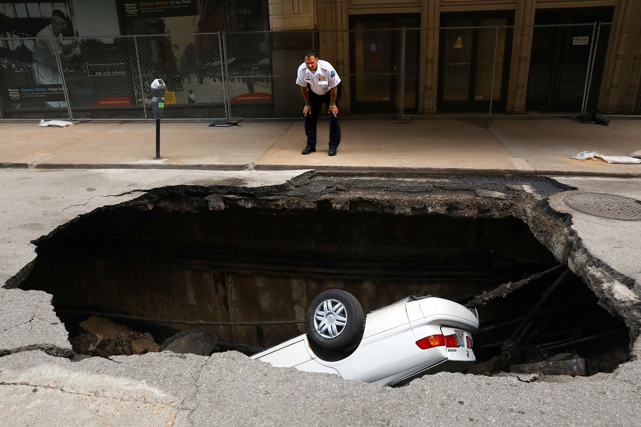 A St. Louis police officer looks over a large hole in 6th Street, Thursday, June 29, 2017, in St. Louis, that swallowed a Toyota Camry between Olive and Locust Streets. It isn't immediately clear what caused the collapse.