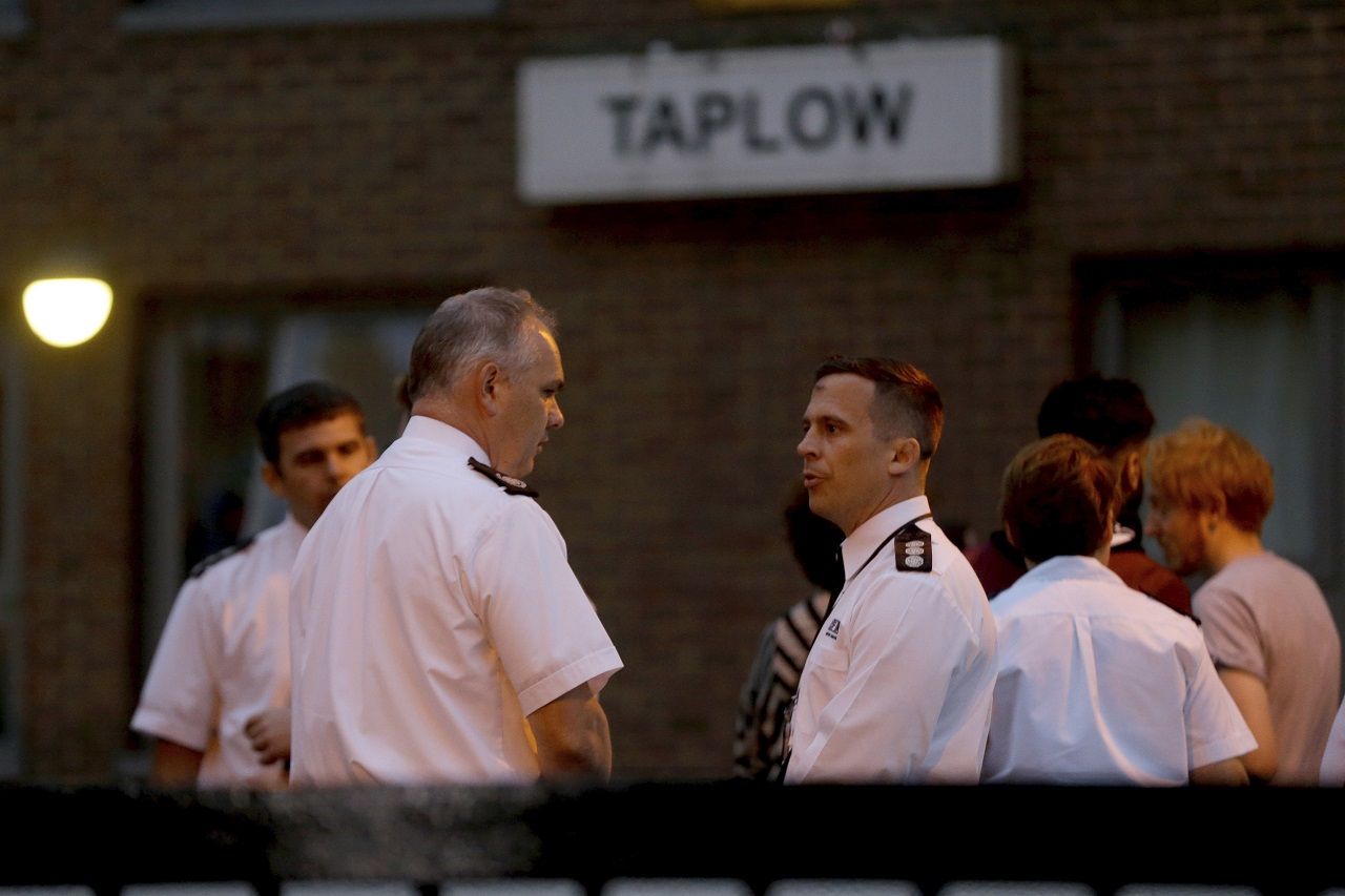 London fire brigade officers speak to each other as residents are evacuated from the Taplow residential tower block on the Chalcots Estate, in the borough of Camden, north London, Friday, June 23, 2017. A local London council has decided to evacuate some 800 households in apartment buildings it owns because of safety concerns following the devastating fire that killed 79 people in a west London high-rise.