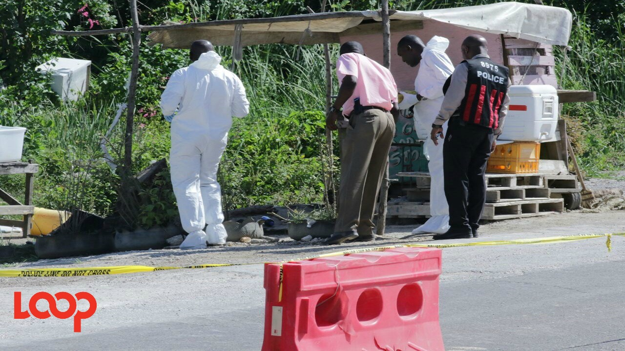 Investigators process the scene where a vendor was shot and killed along the Mandela Highway on Wednesday.