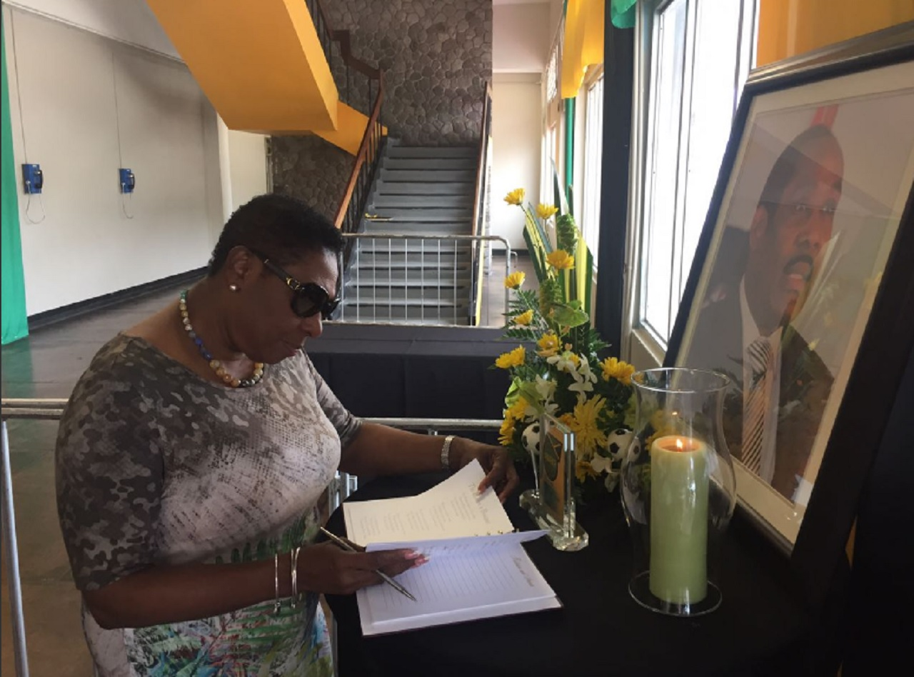Sports Minister Olivia Grange signs the condolence book for the late Jamaica Football Federation's president Captain Horace Burrell at the National Arena in Kingston on Tuesday.