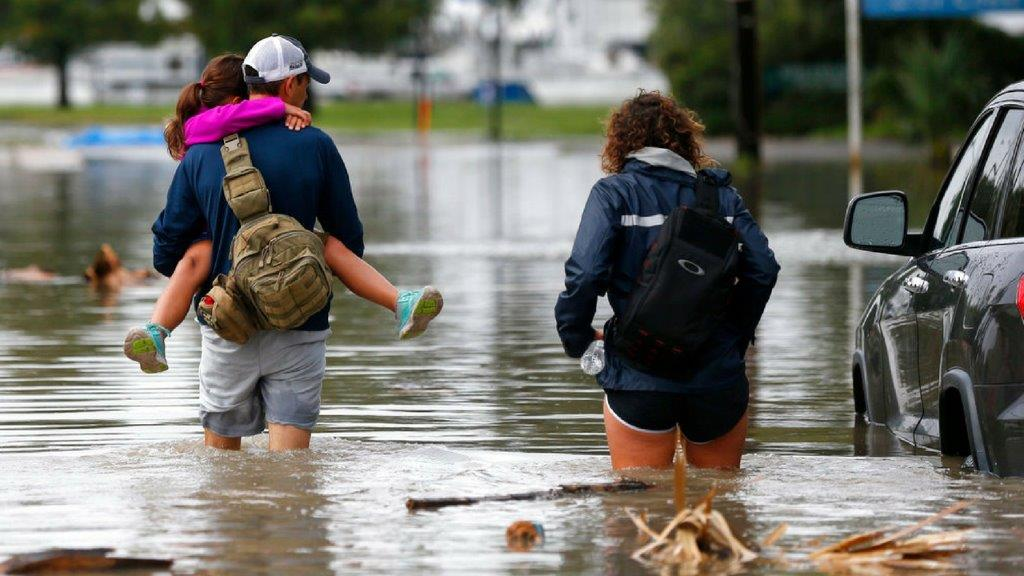 Don Noel carries his daughter Alexis, 8, with his wife Lauren, right as they walk through a flooded roadway to check on their boat in the West End section of New Orleans, Wednesday, June 21, 2017. Tropical Storm Cindy formed Tuesday in the Gulf of Mexico, hovering south of Louisiana as it churned tides and spun bands of heavy, potentially flooding rain onto the central and eastern Gulf Coast. (AP Photo/Gerald Herbert)