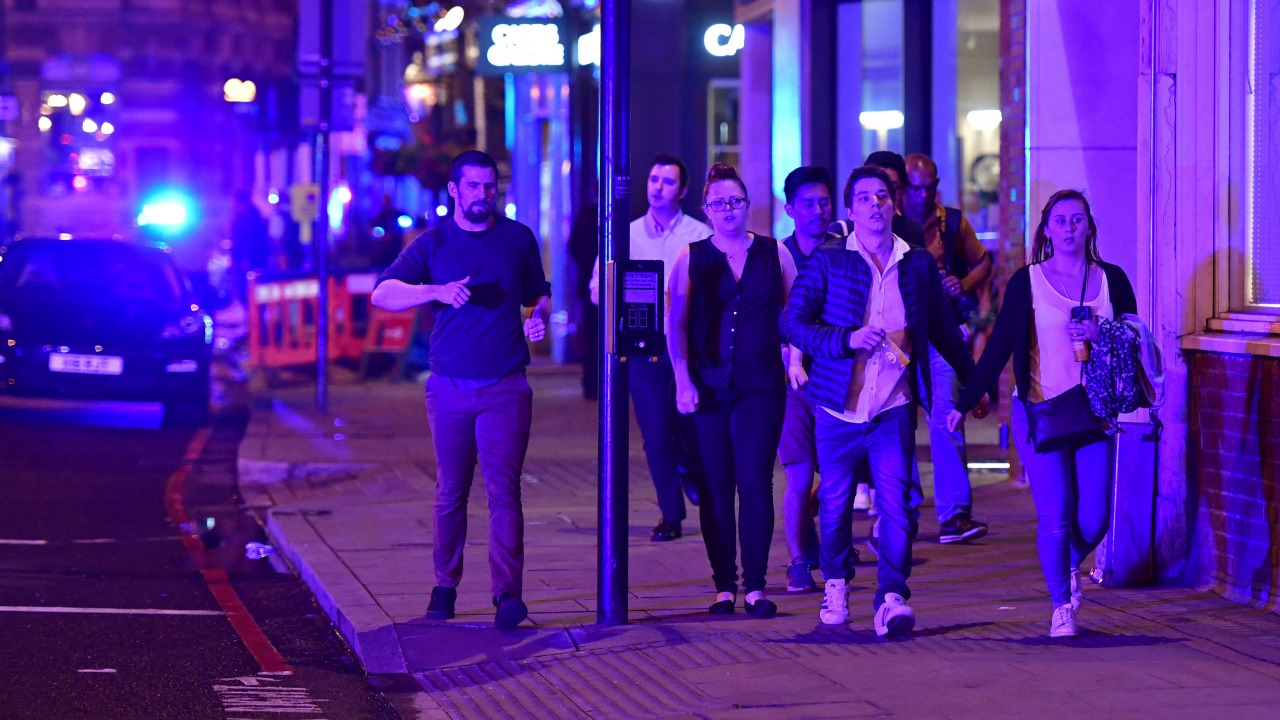 "People run down Borough High Street as police are dealing with a ""major incident"" at London Bridge in London, England on Saturday, June 3, 2017. (Dominic Lipinski/PA via AP)"