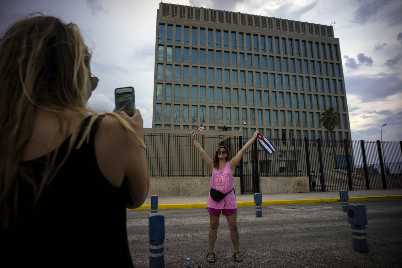 In this Aug. 11, 2015 file photo, US Citizen Jordan Graddis, 24, left, takes a photo of Emily O'connell, 24, as she holds a US and a Cuban flag in front of the U.S. embassy in Havana, Cuba.