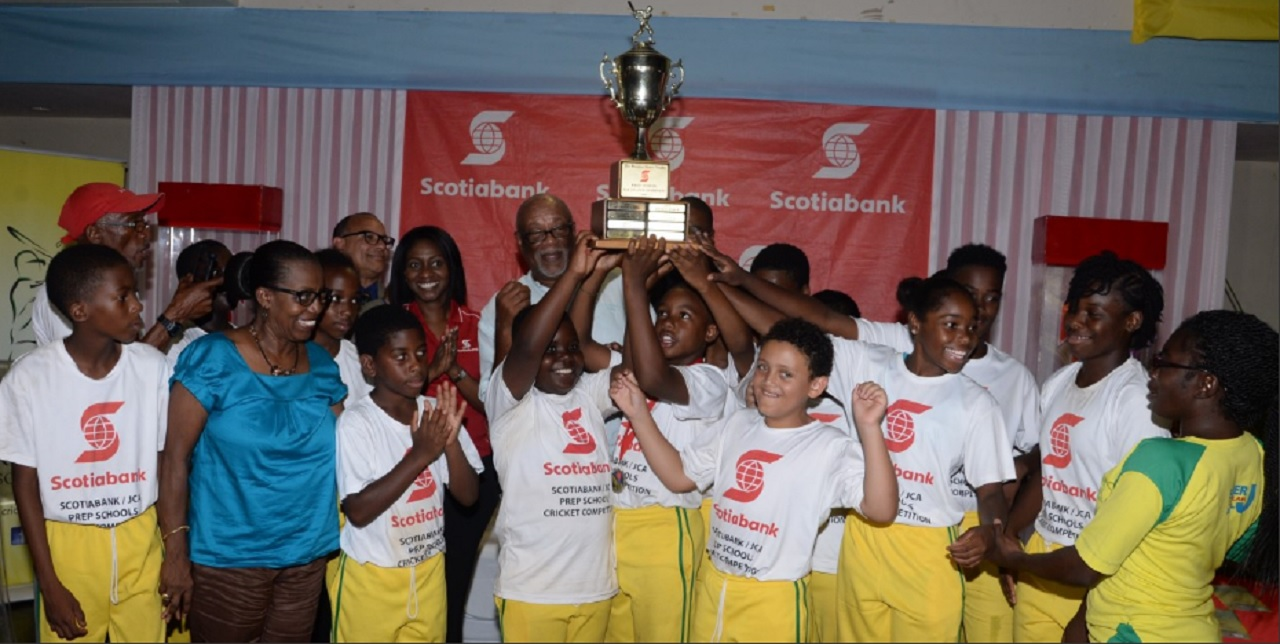Members of Belair cricket team celebrate with the championship trophy after winning the Scotiabank Prep School Cricket Competition on Thursday at Sabina Park.