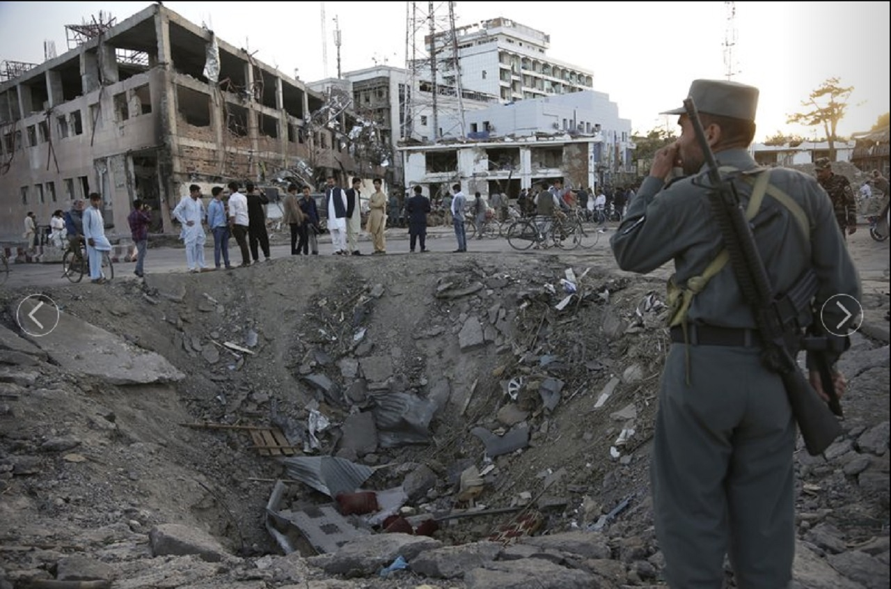 Security forces stand next to a crater created by massive explosion in front of the German Embassy in Kabul, Afghanistan, Wednesday, May 31, 2017.
