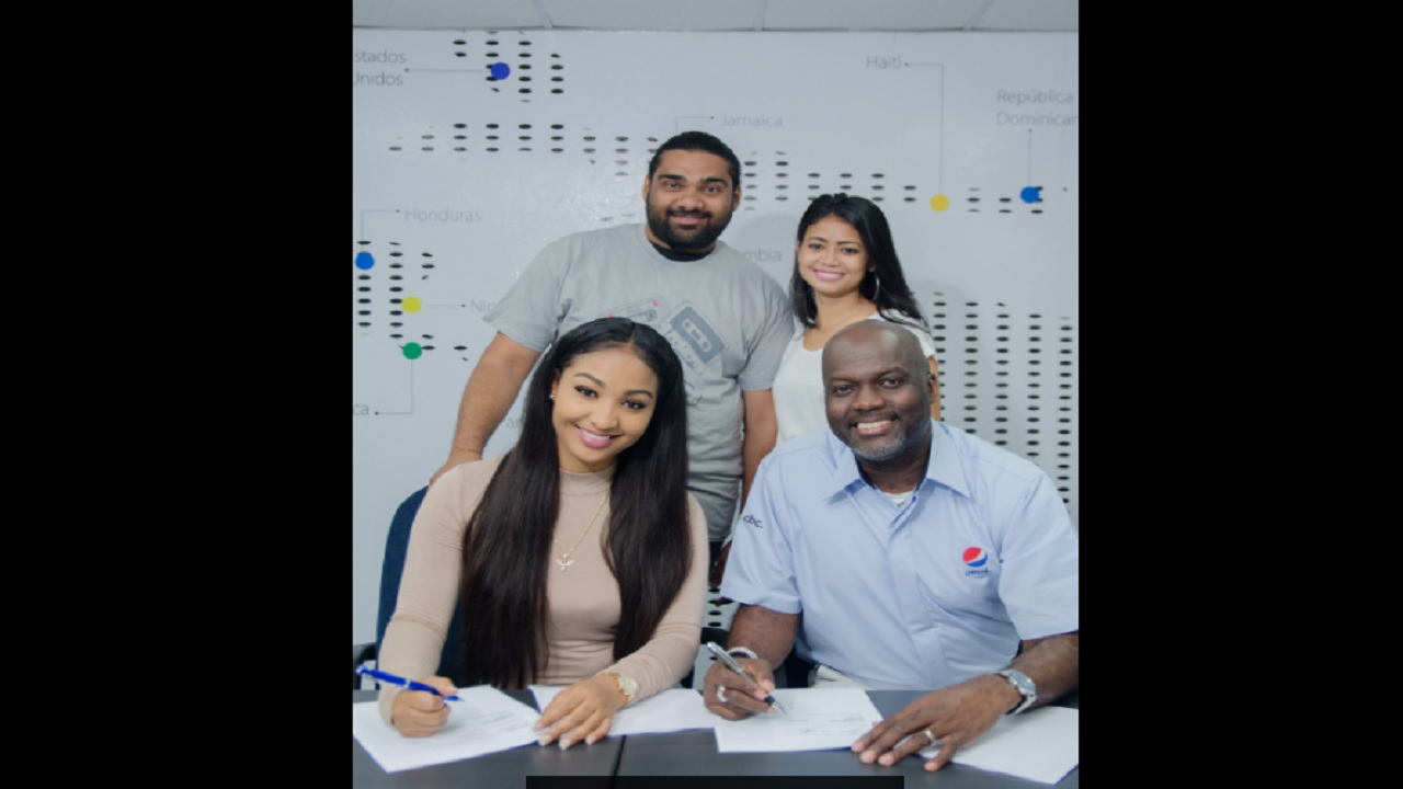 Mitchell Watson (front right), Marketing Manager, Pepsi-Cola Jamaica is all smiles with dancehall artiste Shensea (front left) after officially signing endorsement contract with the 20-year old fast-rising singjay. Looking on are Elizabeth Swaby, Brand Manager, Carbonated Beverages and Romeich Major, Chief Executive Officer, Romeich Entertainment.