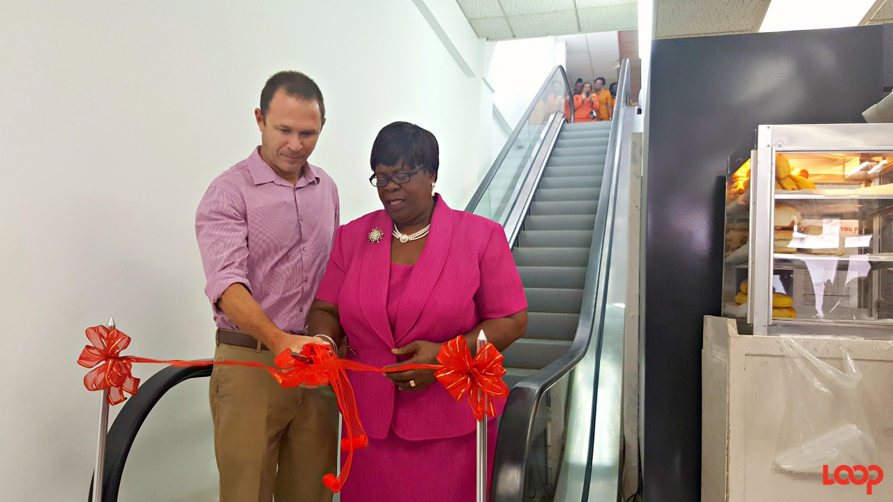 Managing Director Martin Bryan cutting the ribbon to open access to the new escalator to the public, along with the most recent retiree Irma Adams.