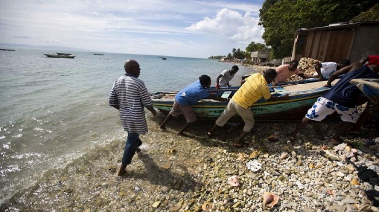 Haitian fishermen move their boats out of the water. (PHOTO: AP)