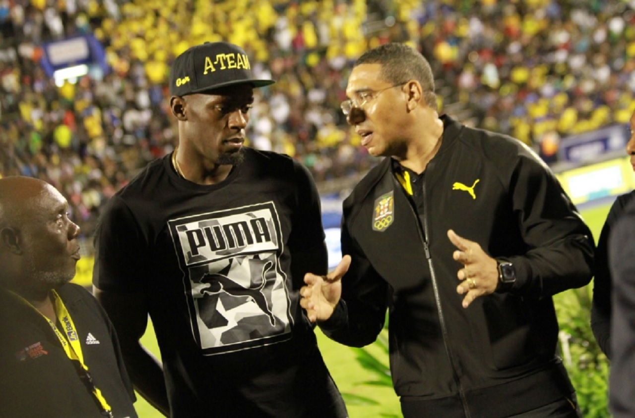 Prime Minister Andrew Holness (right) gets the full attention of Usain Bolt and his coach Glen Mills. Occasion was Saturday's JN Racers Grand Prix at the National Stadium - Bolt's final race on home soil.